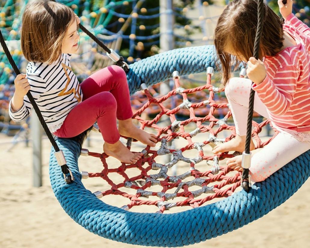 Spielplatzkontrolle Software/APP: Bild von 2 Kindern, die auf einer Spielplatzschaukel schaukeln